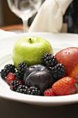 Teller mit frischen Beeren, Pflaume und grünem Apfel