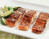Three Fillets of Glazed Grilled Salmon on a Platter with Limes