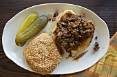 Open Sloppy Joe on a Plate with Pickles