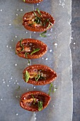 Dried tomatoes with herbs and sea salt on baking parchment