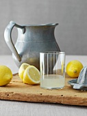Glass of Fresh Squeezed Lemon Juice; Lemons and Juicer