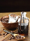 A bottle of coffee & vanilla liqueur with coffee beans & sugar