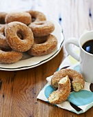 Plate of Sugar Donuts, Halved Donut on Napkin with Coffee