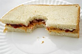 Halbes, angebissenes Erdnussbutter-Marmelade-Sandwich