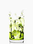 Ice Splashing into a Glass of Green Liquid