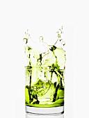 Eiswürfel fällt in Glas mit grüner Flüssigkeit
