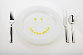 Corn Kernels Forming a Smiley Face on a White Dinner Plate