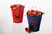 Red and Blue Pails Filled with Cherries; White Background