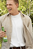 Man Holding a Bottle and Laughing Outdoors