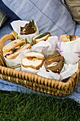 Assorted Wrapped Sandwiches in a Picnic Basket on the Grass