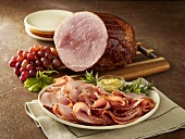 Kurobuta Ham with Grapes on Cutting Board, Sliced on a Plate