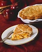 Ein Stück Apple Pie, eine ganze Pie und Äpfel