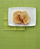 Grilled Ham and Cheese Sandwich; Halved on Plate
