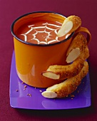 Bread Stick Fingers Grasping Mug of Pumpkin Soup