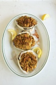 Three Stuffed Clams on a  Plate with Squeezed Lemon Wedges