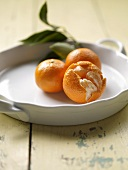 Three Tangerines; One Split Openl On White Dish