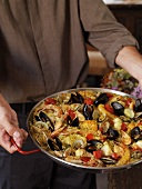 Person Carrying a Pan of Paella