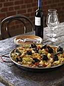 Paella on a Rustic Woden Table with Wine