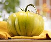 A Green Tomato on a Dish Cloth