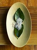 Rock Salt on Leaves on Wooden Platter