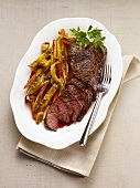 Partially Sliced Steak on a Plate with Roasted Vegetables