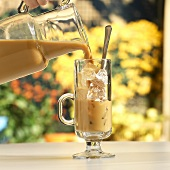 Ice Coffee Pouring into a Glass from Pitcher
