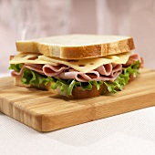 Ham and Swiss Sandwich on White Bread on Cutting Board