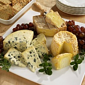 Three French Cheeses on a Board with Grapes