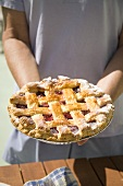 Person Holding Lattice Top Cherry Pie