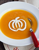 Bowl of Pumpkin Soup with Cream Garnish