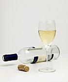 Eine leere Weissweinflasche liegt neben vollem Glas