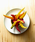 Red, Yelllow and Orange Chili Peppers Sticking Out of Mug