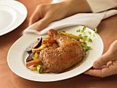 Hände servieren Teller mit Hähnchenkeule und Gemüse