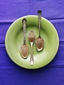 Three Spoon Madeleines with Powdered Sugar on Green Plate