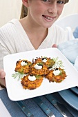 Girl Holding Plate of Carrot Latke with Wasabi Cream and Caviar