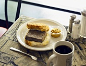 Fried Livermush Biscuit with Mustard and Coffee on Cafe Table
