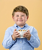 Little Boy Holding Bowl of Cereal with Fruit