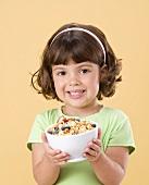 Mädchen hält eine Schüssel mit Fruchtmüsli