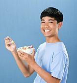 Boy Holding Bowl and Spoon of Cereal