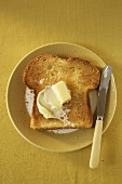 Piece of Toast with Butter on Plate; Knife