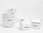 White Coffee Mugs; Cream and Sugar Containers; Labeled
