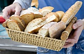 Hände halten Körbchen mit Artisan-Broten