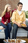 Man and Woman Tailgating with Beer and Sandwiches