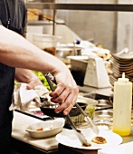 A Chef Plating Food in a Restaurant Kitchen