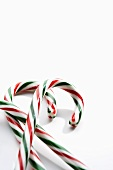 Three Red and Green Striped Candy Canes on White