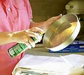 Woman Spraying Cake Pan with Non-Stick Spray
