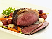 A Whole Chuck Roast, Partially Sliced on a Platter with Veggies