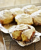 Frosted Cinnamon Buns on Foil on Cooling Rack