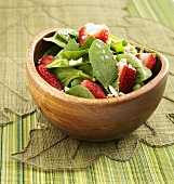 Spinatsalat mit Erdbeeren in Holzschale
