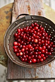 Cranberries in Colander on Wooden Table